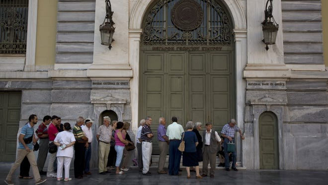 Pensioners line up at the main gate of the national bank of Greece in Athens on July 7, 2015.