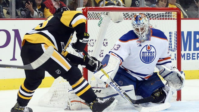 Oilers goalie Cam Talbot (33) makes a save against Penguins forward Conor Sheary during the second period.