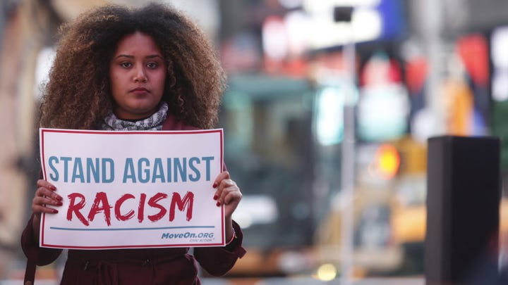 "Members of MoveOn.org Political Action stand outside the studios of ""Good Morning America"" with signs saying ""stand against racism"" in New York City on March 16, 2016."