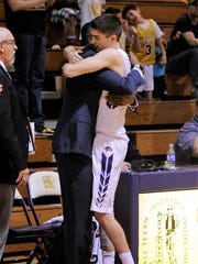Hardin-Simmons senior Caleb Spoon (2) hugs assistant coach Derrick Jefferson after coming out for the final time of his career. Spoon scored a game-high 29 points as the Cowboys defeated McMurry 90-84 at the Mabee Complex on Saturday, Feb. 17, 2018.