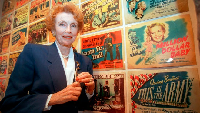 "In this May 14, 1998 file photo, Joan Leslie stands near the movie poster for Irving Berlin's ""This is the Army"" in which Leslie starred with Ronald Reagan, at the museum on the Warner Bros. lot during a tour marking the film studio's 75th anniversary in Burbank, Calif."