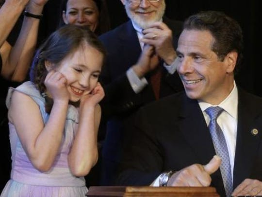 Amanda Houser was standing next to Gov. Andrew Cuomo on July 7 during a symbolic signing of New York's medical marijuana legislation.