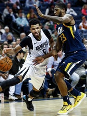 Memphis Grizzlies guard Andrew Harrison (left) drives the lane against Utah Jazz defender Royce O'Neale (right) during third quarter action at the FedExForum in Memphis, Tenn., Wednesday, February 7, 2018.