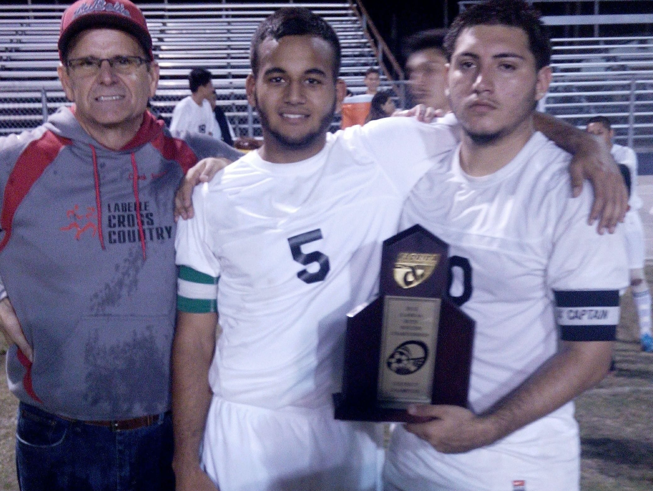 Flavio Soto, right, Christian Galvez, center, and Jef Frost pose for a picture after LaBelle captured the District 2A-12 championship against Clewiston.