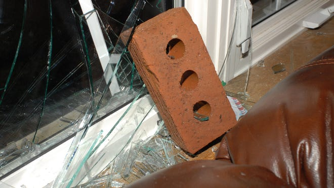 This image shows a brick that was thrown through a window in Little Chute.