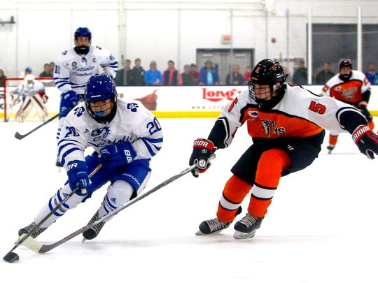 Catholic Central's Mitch Morris (left) tries to turn the corner on Rice defenseman Will McLellan.