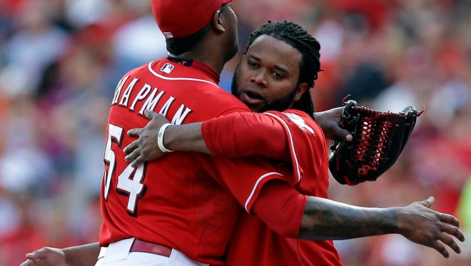 Cincinnati Reds starting pitcher Johnny Cueto, right, hugs relief pitcher Aroldis Chapman (54) after they defeated the Pittsburgh Pirates.