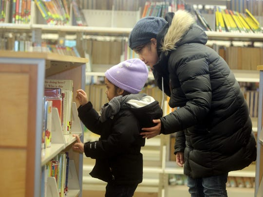 Elizabeth Garcia helps her daughter Natalie Collado, 6, pick out a book at the Yonkers Public Library's Riverfront branch.