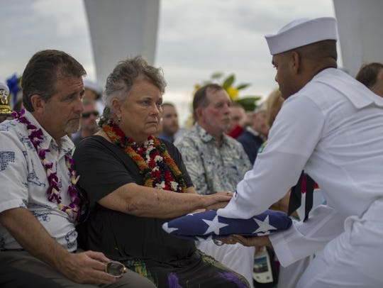 A sailor presents the American flag to the family of