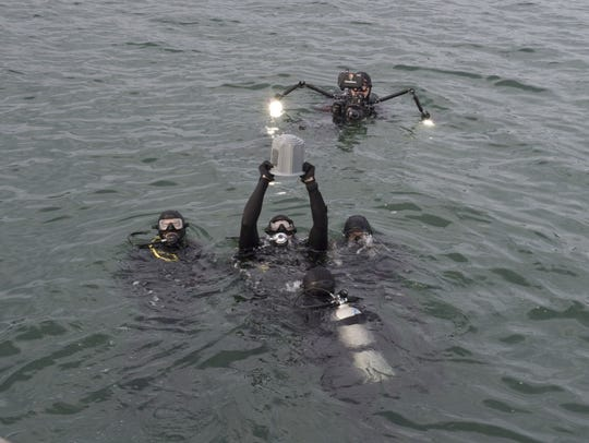 Navy and National Park Service divers prepare ashes