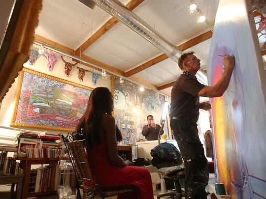"Artists Lon Michels, 52, paints a portrait of model Melissa Ballard, 40, of Indio, in his recently opened art gallery in Palm Springs. The painting is Michels' reproduction of the 1656 painting by Diego Velasquez ""Las Meninas."""
