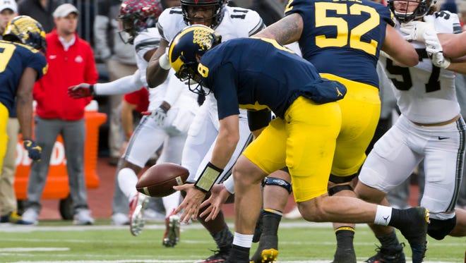 Michigan quarterback John O'Korn fumbles the ball in the second quarter.