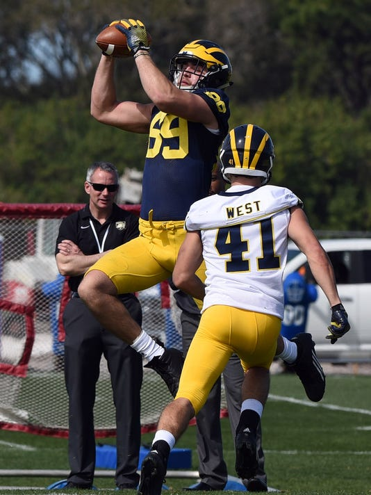 University of  Michigan NCAA college football player Ian Bunting leaps for a catch with Ryan Tice (41) during a workout at IMG Academy in Bradenton, Fla., Monday, Feb. 29, 2016. (Tiffany Tompkins/Bradenton Herald via AP)  SARASOTA HERALD-TRIBUNE OUT; TAMPA TRIBUNE OUT; MANDATORY CREDIT