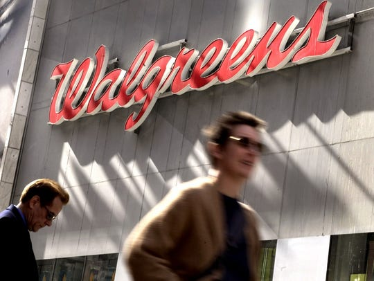 People pass by a sign outside a Walgreens store.