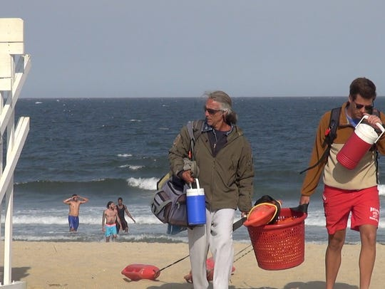 Lifeguards grab their gear and head for the street