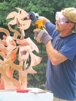 Asheville-based artist David Sheldon focuses his attention on an original sculpture piece.