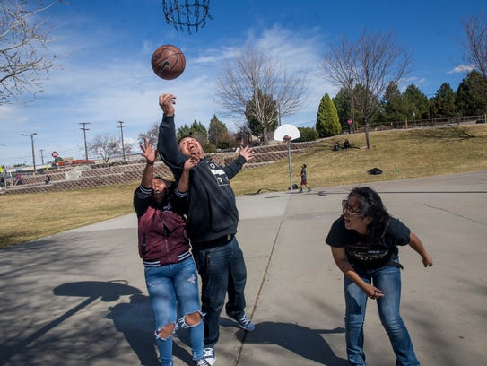 At center, Martin Begaii plays basketball with his daughters Tenaya Begaii, left, and Kiona Trujillo, right, Monday at the basketball courts at Brookside Park in Farmington.