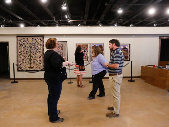 Farmington Museum at Gateway Park staff members Adrienne Boggs, left, Tasha Soce, Amy Homer and  Jeffery Richardson examine the rugs on display Thursday at the Museum of Navajo Art and Culture in Farmington.