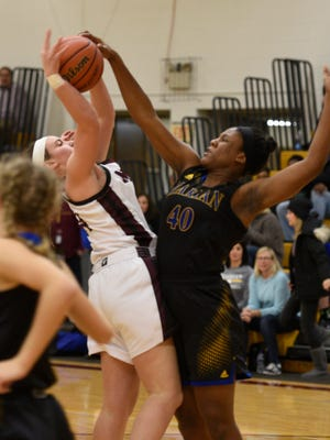 Providing some tough defense for Marian is Uche Ike (left) against Mercy's Kulia Bishop.