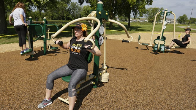 Christine Boushley works on the arm press in the exercise area of the Winnebago County Community Park on Wednesday. The exercise area is west of the beach house.