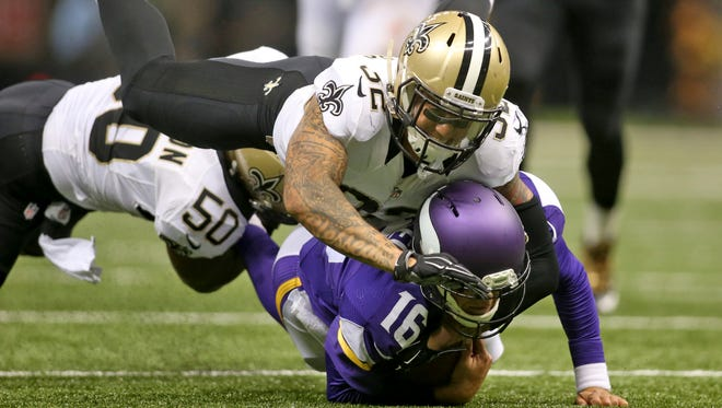New Orleans Saints strong safety Kenny Vaccaro (32) and middle linebacker Curtis Lofton (50) tackle Minnesota Vikings quarterback Matt Cassel (16) in the first half at Mercedes-Benz Superdome.