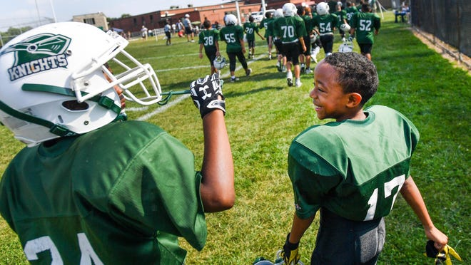 A pair of Richwoods JFL players laugh during halftime of a game against Canton. The JFL of Central Illinois will suspend registration fees for 2020 because of the coronavirus pandemic.