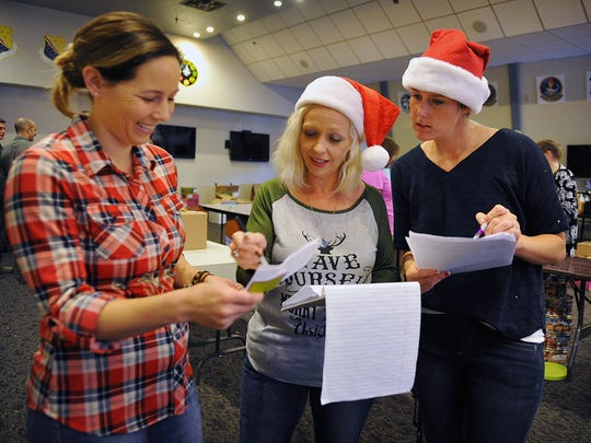 Jenni Pargas, left, Tiffany Kelley and Ashley Brink look over donations for the annual Cookie Drive organized by the Sheppard Enlisted Spouses Club at Sheppard Air Force Base.