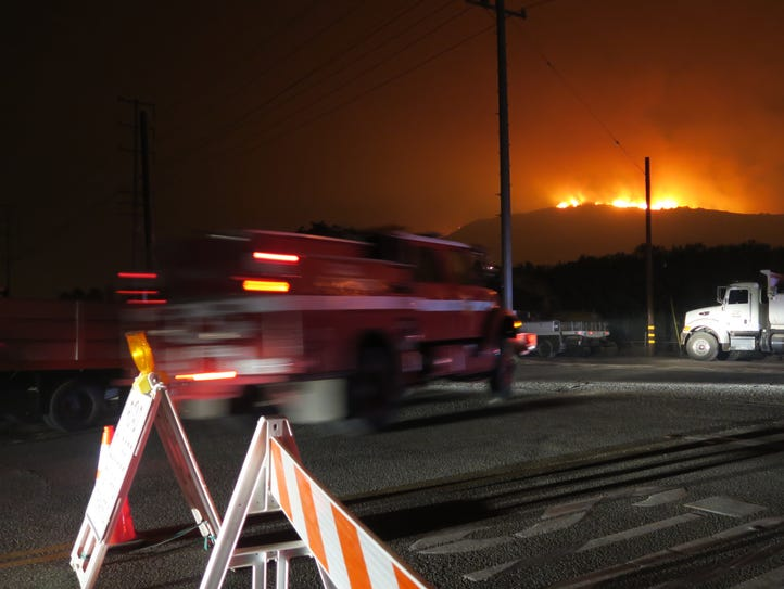 A fire truck goes by as flames can be seen in the distance