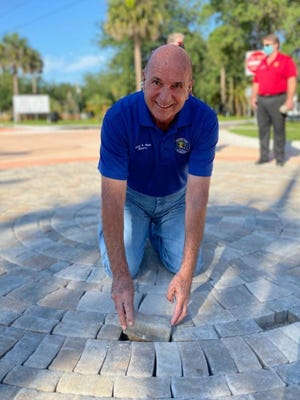 Orange City Mayor Gary Blair places one of the final pavers into the brick medallion at East Graves and Holly avenues as part of the Holly Avenue Streetscape project, which was the city's first major Community Redevelopment Agency endeavor.