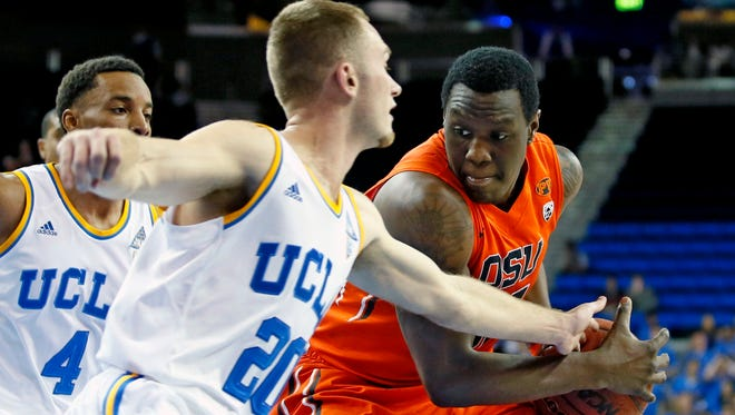 Oregon State's Jarmal Reid, right, goes to the hoop as UCLA's Bryce Alford, left, defends him during the first half of an NCAA college basketball game Wednesday, Feb. 11, 2015, in Los Angeles.