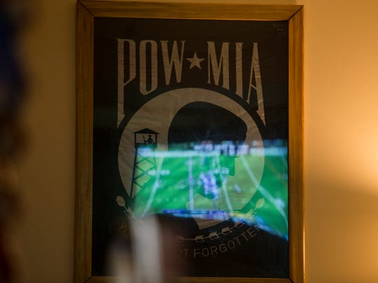 The Minnesota Vikings game is reflected in a POW/MIA poster at the American Legion Walter L. Fox Post #2 Sunday in Dover. NFL viewership the post has dropped significantly since players began taking a knee in protest during the national anthem. The change has hurt the post's income greatly.