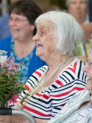 Founder of the Interfaith Food Pantry of Portage County Mary Wright receives flowers during the grand opening ceremony for the new location at 2810 Post Road in Plover.