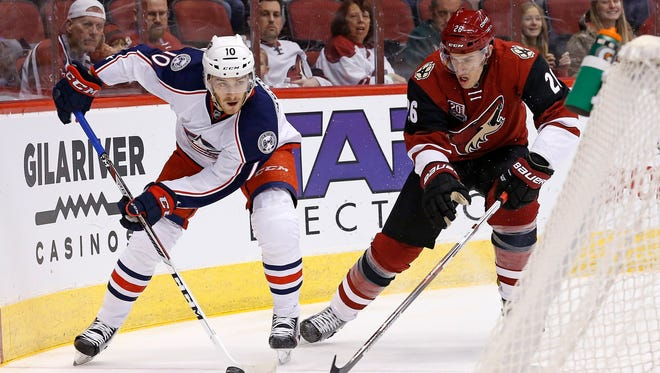 Columbus Blue Jackets center Alexander Wennberg (10) controls the puck in front of Arizona Coyotes defenseman Michael Stone (26) during the first period of an NHL hockey game Saturday, Dec. 3, 2016, in Glendale, Ariz.