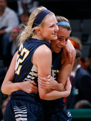 Haslett's Kenzie DeCook, left, and Adrianna Stolicker hug as they come off the court in the final moments of their 63-52 win over Benton Harbor.