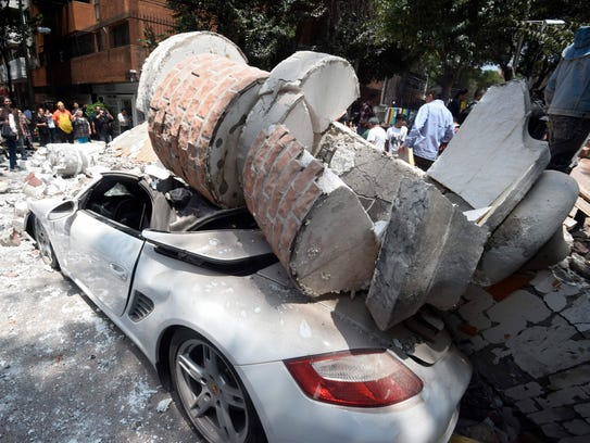 A car crashed by debris from a damaged building after