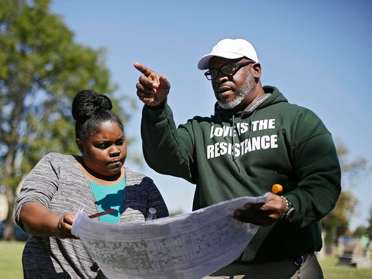 Kristi Williams, left, and Chief Egunwale Amusan view a cemetery map Monday during a search for possible mass burial graves from Tulsa's 1921 Race Massacre at Oaklawn Cemetery in Tulsa, Okla.