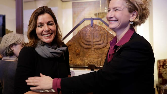 The director of the Vatican Museums, Barbara Jatta, left, and the director of Rome's Jewish Museum, Alessandra Di Castro, pose for a photo in front of a bas-relief showing a menorah at the end of a news conference in Rome on Feb. 20.