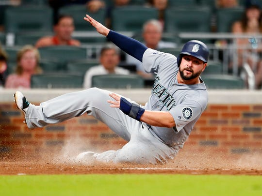Seattle Mariners Yonder Alonso avoids the tag at home to score in the fourth inning against the Atlanta Braves, Monday, Aug. 21, 2017, in Atlanta.