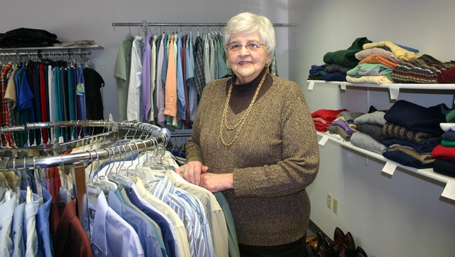 Volunteer Pat Raymond stands among the clothing offered at Career Closet.