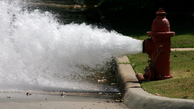 A photograph taken of a fire hydrant releasing some pressure one hot Oklahoma day.
