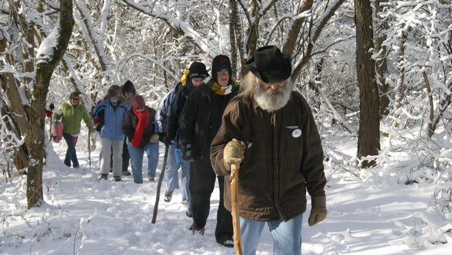 Denny Jernigan, a volunteer for Hamilton County Great Parks, leads hikers along a snow-covered trail in Woodland Mound in 2009. Organizers have been surprised that despite the weather, there has been good attendance at the Winter Hike Series for 30 years.
