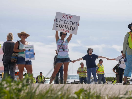 Sarah Bass of Boone, Iowa, holds a sign against eminent domain abuse as more than 100 protesters gathered to voice their opinion against the development of the Bakken Pipeline during a rally on Wednesday, Aug. 31, 2016, in Boone.