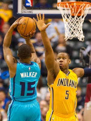 Indiana Pacers forward Lavoy Allen (5) stretches out in an effort to block the shot of Charlotte Hornets guard Kemba Walker (15) during the first half of an NBA basketball game, Friday, April 3, 2015, in Indianapolis. Pacers led at the half 49-38.