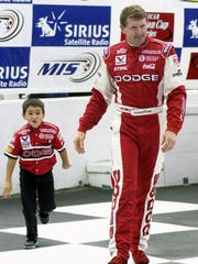 Bill Elliott, right, leads his son from driver introductions for the Sirius Satellite Radio 400 at Michigan International Speedway in Brooklyn, Mich., Sunday, June 16, 2002.