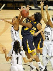 Pocomoke's Dynaisha Christian, center, shoots against Forestville's Kristen Horne, top left, and Carrie Gross at SECU Arena in Towson last season.
