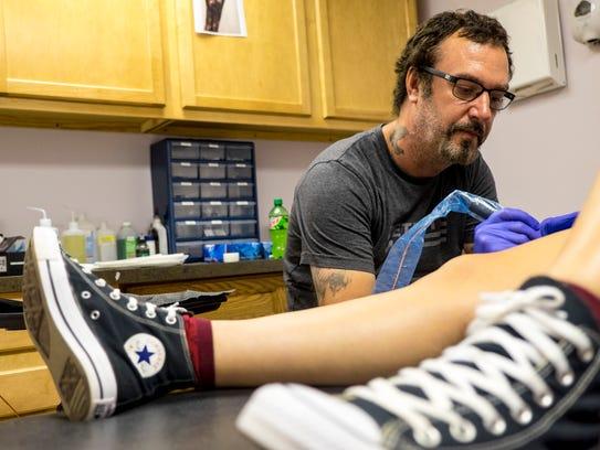 Robert Hulvey tattoos a moth on Madison Revels, 16,