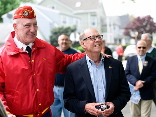 Paul Chepurko, left, leads Bruce Mahnken Jr. to the street dedication Monday in honor of his father.