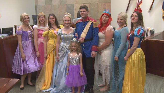 Danielle Koning, 5, poses for pictures with all of the Disney princesses and Prince Charming on Wednesday, June 8, 2016, in the middle of Kent County's 17th Circuit Court in Grand Rapids, Mich. The characters surprised Danielle during her adoption finalization hearing.