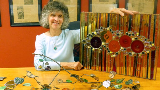 Sandy Hartley shows one of her free form branches of glass leaves and a unique glass panel design.