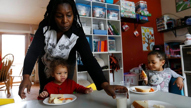 Tonja Boggs serves up milk and snacks to her day care children Feb. 11, 2016, at her home in Des Moines. Boggs has filed a complaint against the city's 483 other state-sanctioned in-home day cares in an effort to force Des Moines officials to revisit the city's rarely enforced rule limiting in-home day cares to six children.